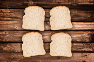 Four slices of bread, on wood planks background