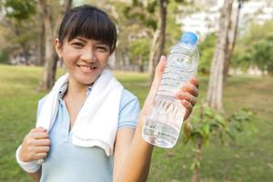 Asian sport woman smiling showing bottle of water