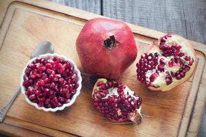 raw pomegranates on a wooden background