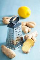 fresh ginger root and grater over blue photo