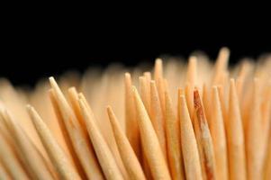 close-up de palitos de dente de madeira em fundo preto