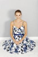 Woman in blue summer dress sitting