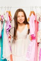 Beautiful girl stands among hangers with clothes photo