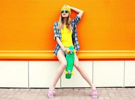 Fashion hipster cool girl in sunglasses and colorful clothes wit