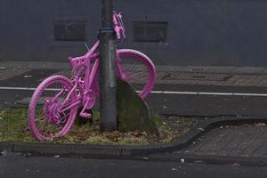 Fahrrad pink vor dunkler Wand photo
