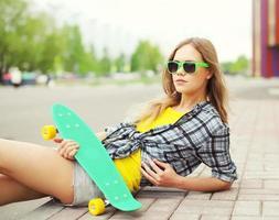 Retrato de moda de chica guapa en gafas de sol con skateboa
