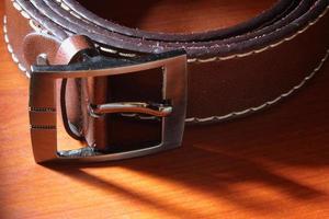 Leather belt on wooden background photo