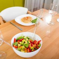Salad on the dinner table with pasta and wine glasses