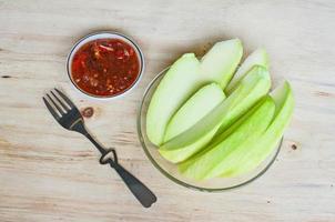 Mango verde fresco en rodajas sobre mesa de madera foto