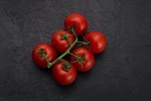 cherry tomatoes on black slate stone