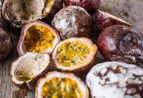 Rotten passion fruit on wooden background photo