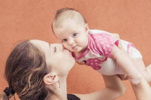 glückliche Mutter, die ihr Baby am Wandhintergrund küsst
