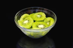 Slices of kiwi on black bowl on