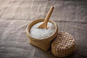 Cucharas de madera y canasta de arroz jazmín en madera