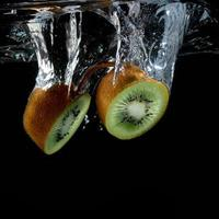 Splashing kiwi fruit on the water