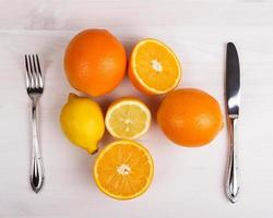 citrus fruits on wooden table. cutlery