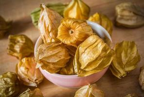 Physalis fruit  in a bowl and on the wooden background photo