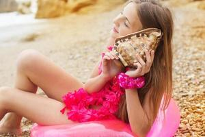 Teen girl is sitting on pink rubber ring with seashell