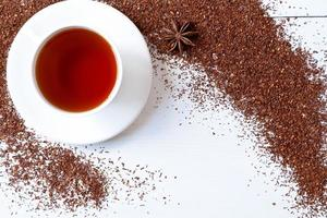 White cup of tasty traditional organic red rooibos tea with photo