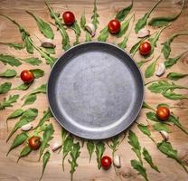 Sartén en blanco tomates hierbas alrededor de texto de lugar, fondo rústico de madera foto