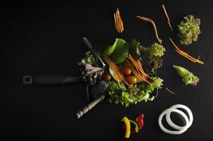 Vegetable salad preparation on black background