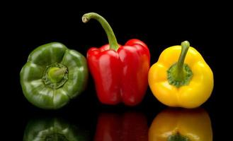 Red,green,yellow bell peppers isolated on black photo
