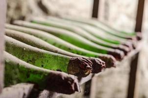 Old dusty wine bottles in cellar photo