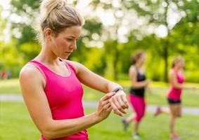 blond woman setting her timer before jogging photo