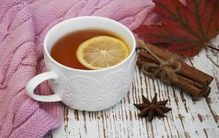 Cup of hot tea with lemon and scarf photo