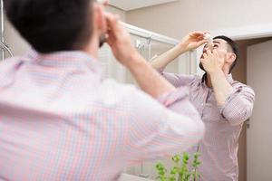 Eye caring with eyedrops photo