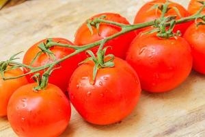 Cherry tomato isolated over a wooden background. photo