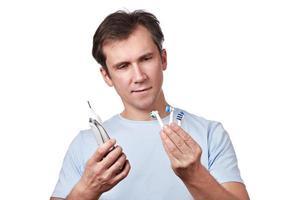 el hombre elige la cabeza intercambiable para el cepillo de dientes eléctrico