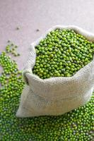 Dried green peas in rustic bag on woody background.