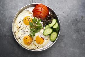 Presentación de huevos cocidos con mentas, tomate, aceituna, pepino y zumaque foto