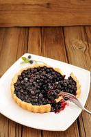 Homemade blueberry tart cut in square white plate with fork