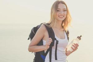 sonriente chica mochilero sostiene una botella con agua
