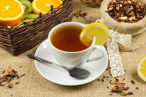 Hot cup of tea, herbal leaves and ripe fruits