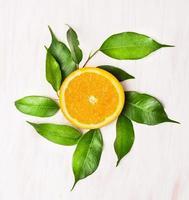 Lóbulo naranja con hojas verdes sobre mesa de madera blanca foto