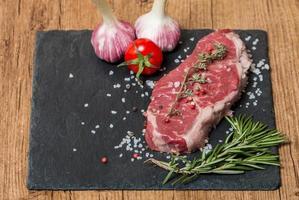 Filete de carne cruda con hierbas frescas y sal foto