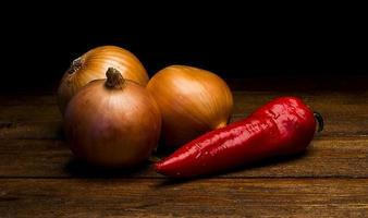 Fresh pepper and onions  on wooden boards photo