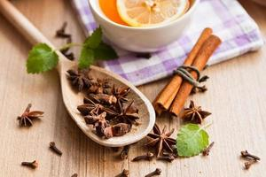 Anise stars, tea and cinnamon sticks on wood photo