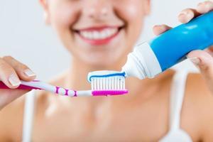 Hermosa joven recogiendo sus dientes. foto