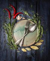 Spoon and Fork on plate with herbs spices frame