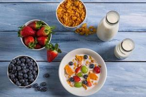 Preparations for breakfast corn flakes and fruits photo