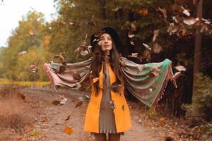 Mujer feliz vomitando hojas de otoño en el parque foto