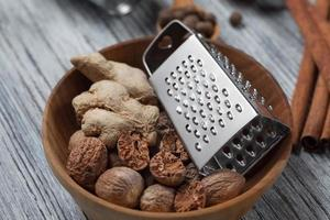 Ginger with nutmeg and grater in bowl on wood