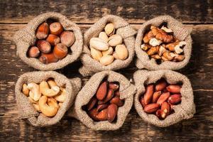 mezclar nueces en la mesa de madera, comida vegana saludable.