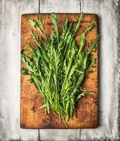Fresh arugula on cutting board and white wooden table