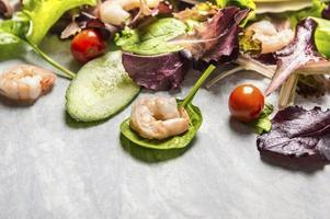Colorful fresh salad with cucumber and shrimps, close up
