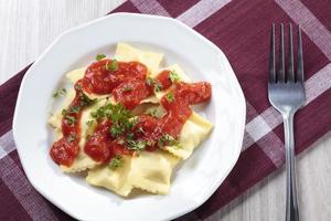 Portion of ravioli with tomato sauce